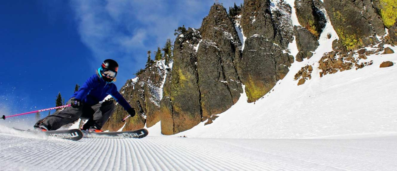 Skier making sharp turn on fresh corduroy