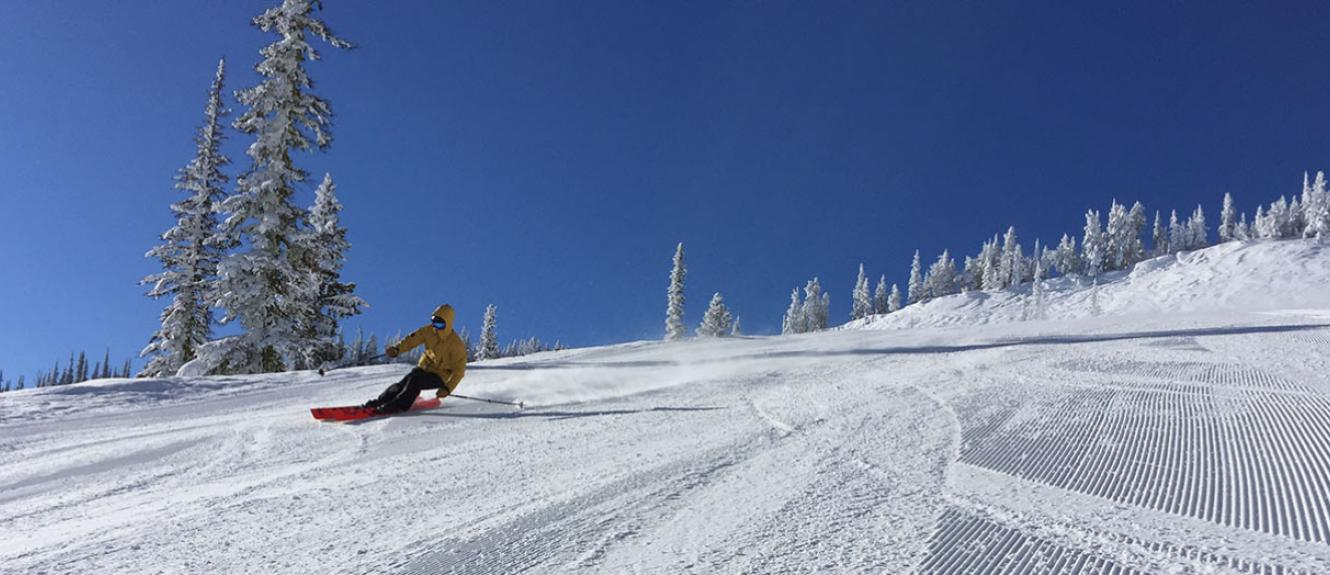 Skier carving turn on groomed run with blue sky behind