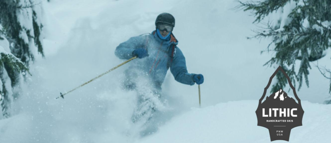 Skier in powder with a Lithic Logo on the left side.