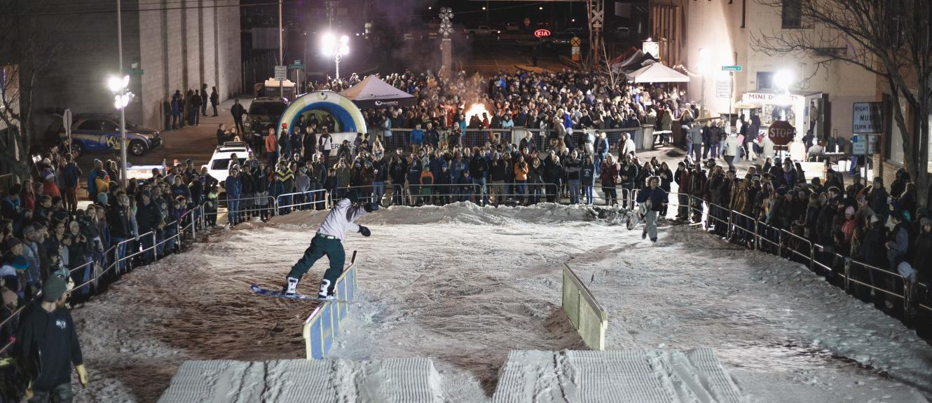 Snowboarder sliding a rail sideways while a large crowd looks on and the Pybus Public Market sign is in the background