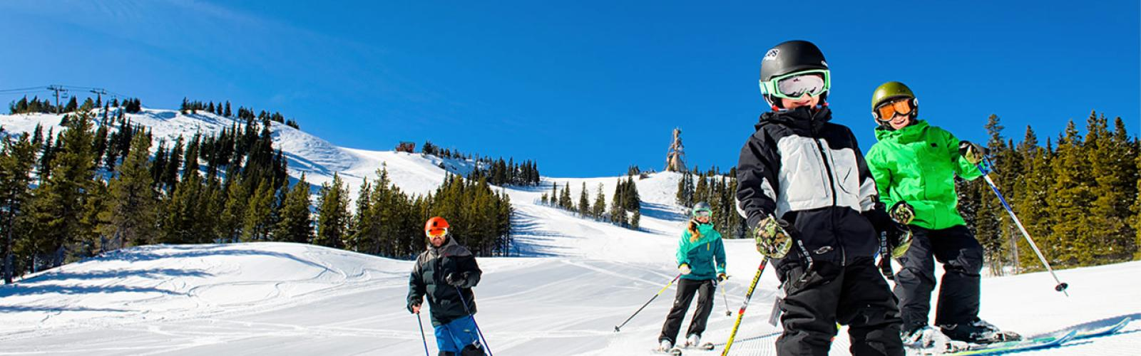 Family of four smiling and skiing on groomed run with blue skies