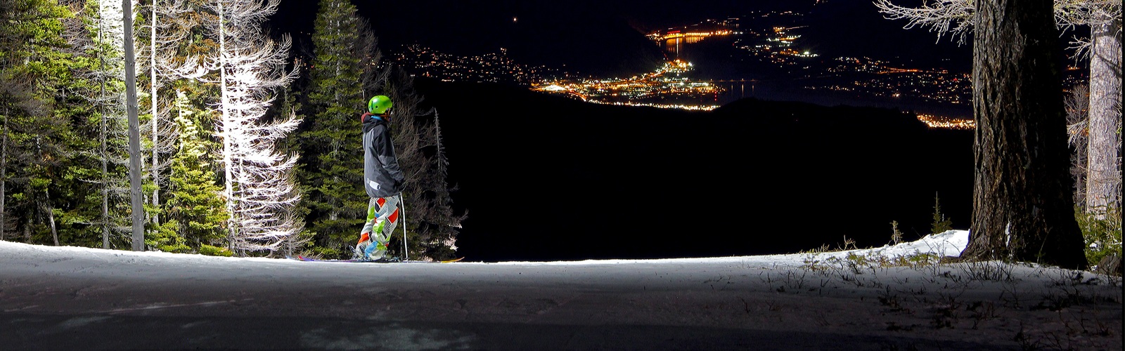 Skier at night with valley lights below