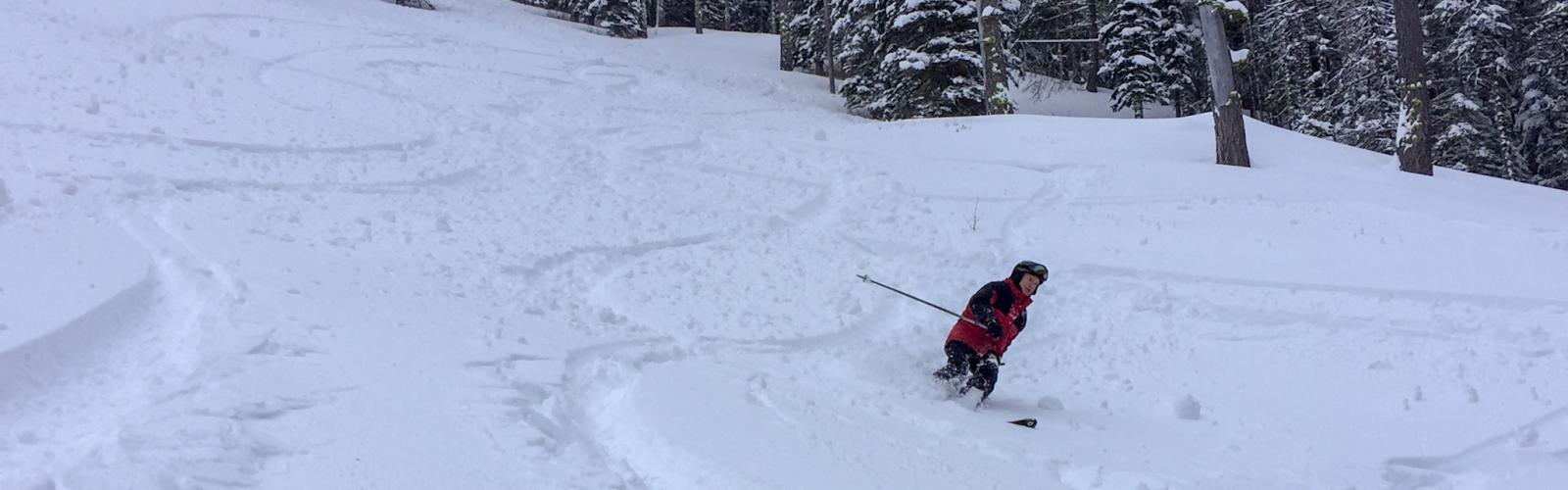 skier in red coat making powder turns
