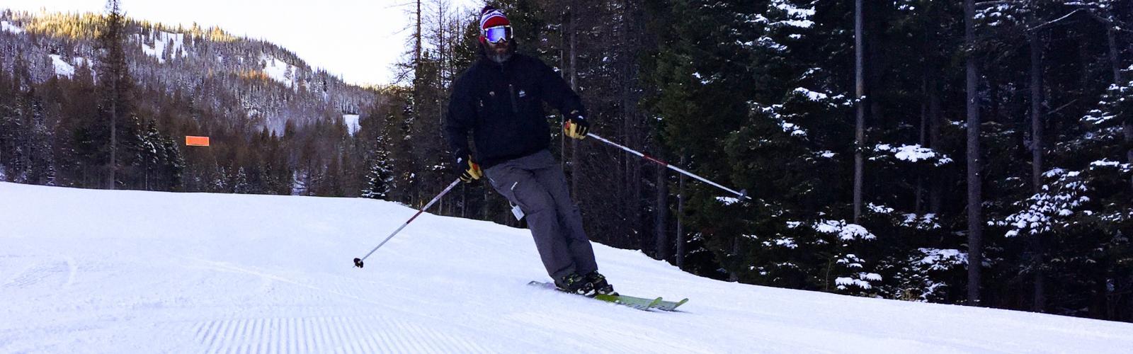 man in black skiing groomed slope