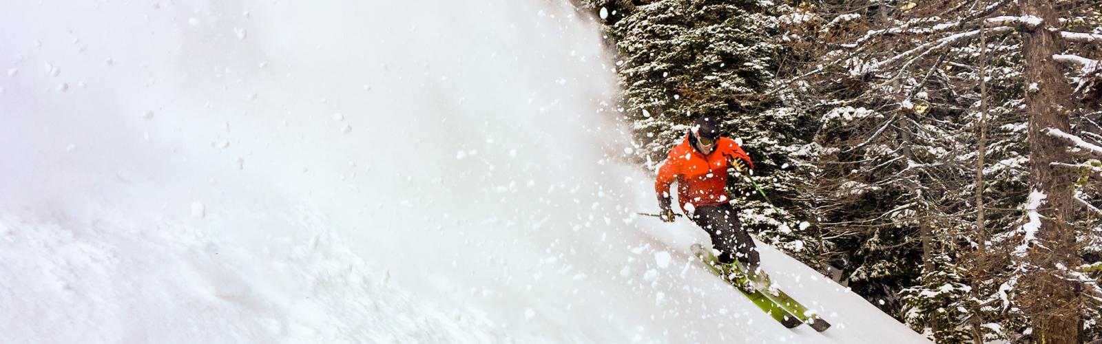 skier escaping his own sluff in front of a big larch