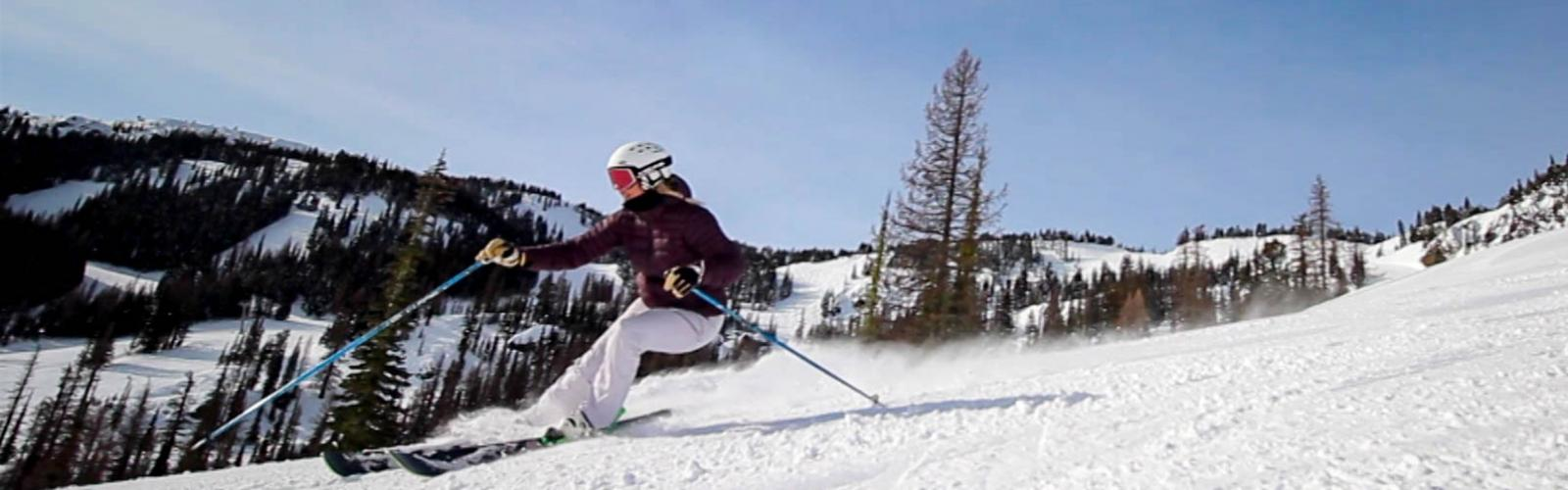 Close up of female skier making turn with ski area behind