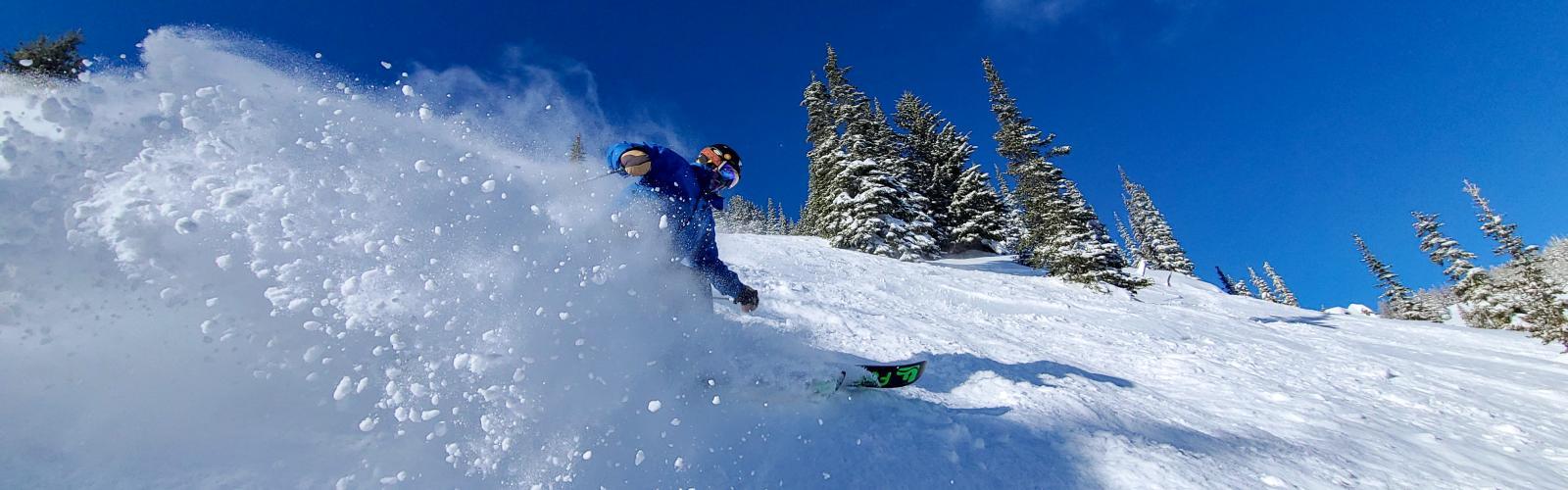 skier making a powder turn on a bluebird day