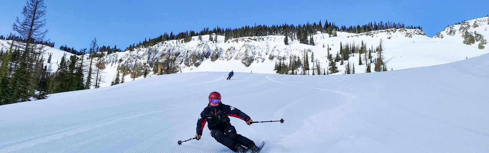 Close up of ski patroller making a turn on fresh corduroy with bomber cliffs in background