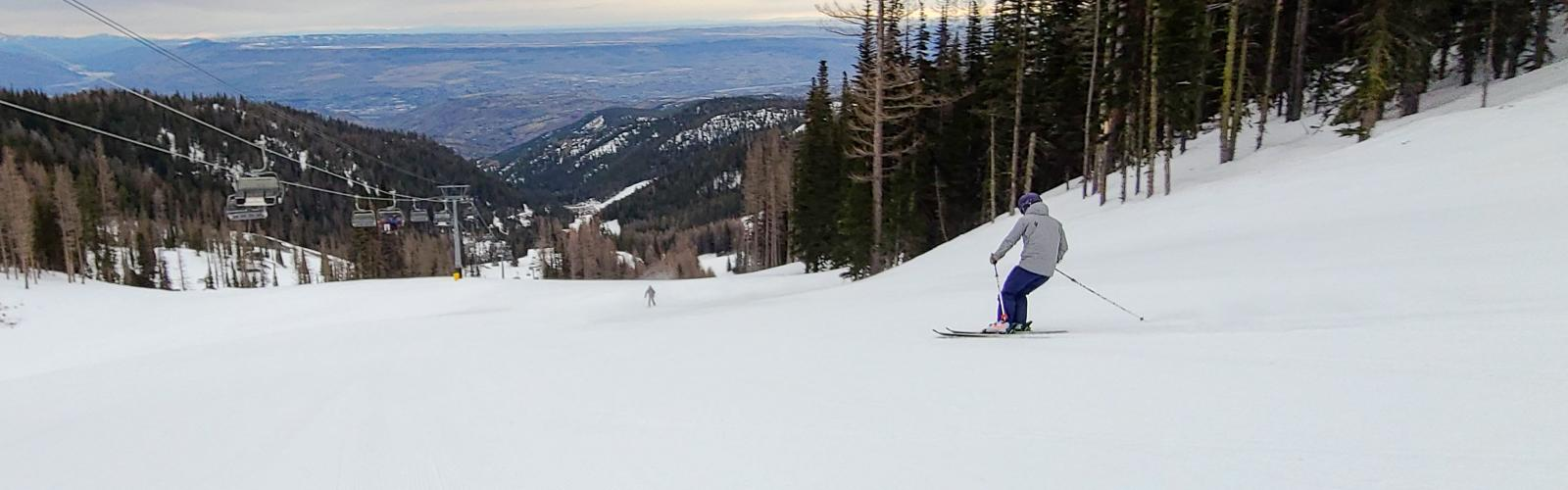 skier making a turn on Tumwater with Wenatchee Express and Valley in the background
