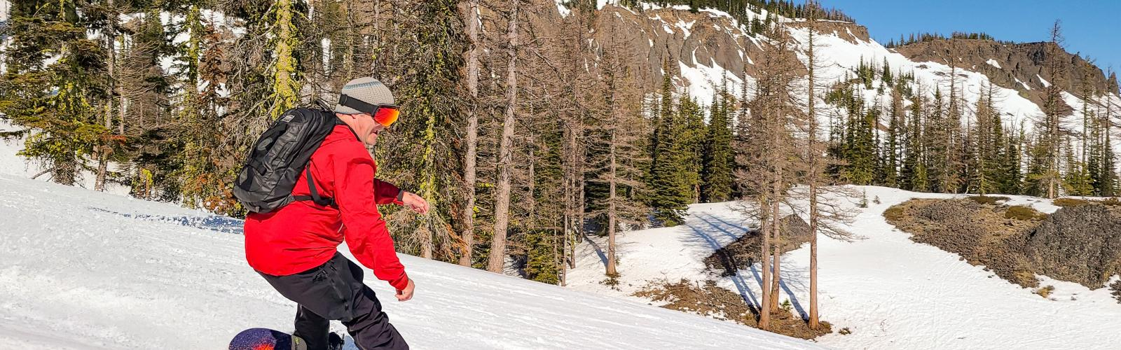 snowboarder smiling while making a turn on a sunny spring day with Bomber cliffs in the Background