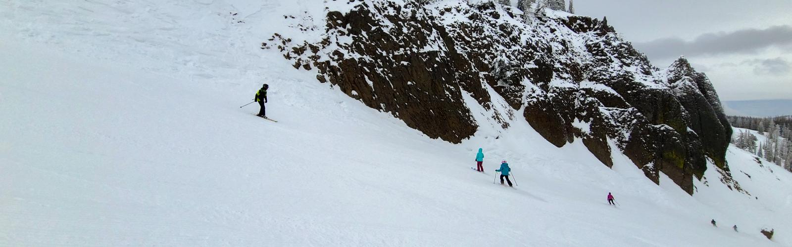 Family skiing down Bomber Bowl run with Bomber Cliffs in the background