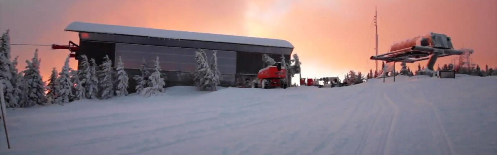 The top terminal of the Wenatchee Express with a lift outside in the snow and sunrise behind