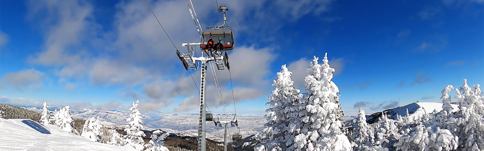 Skiers sitting on the Wenatchee Express with clouds behind them and the valley