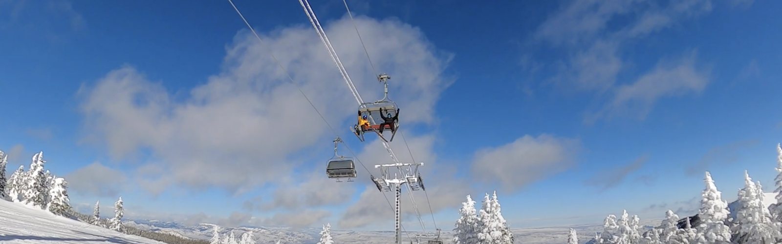two skiers waving from the Wenatchee Express Chair