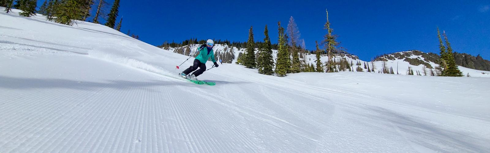 Skier on a groomer with a light dusting of new snow and the bomber cliffs in the background
