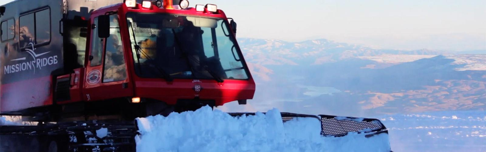 A snowcat pushing snow at the top of the mountain with the valley view in the background