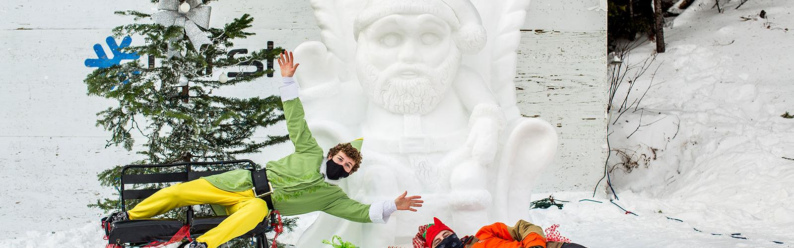 An Elf and a worker laying in front of a snow santa and christmas tree