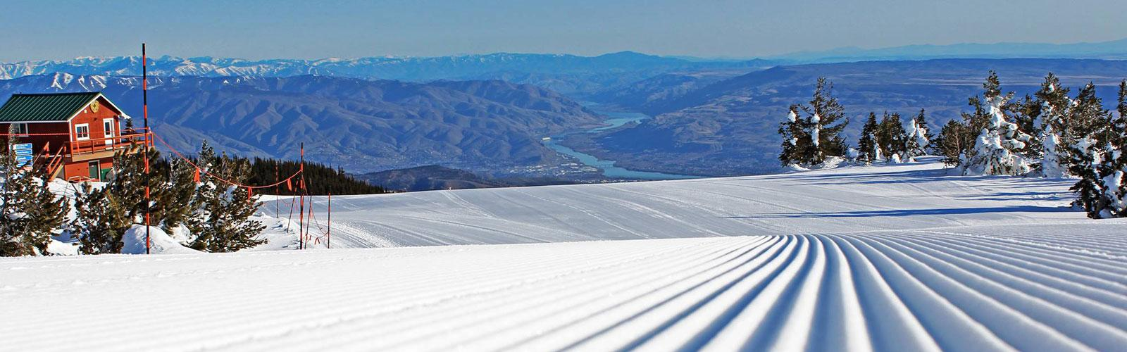 Up close photo of a groomed run with the columbia river in the background.