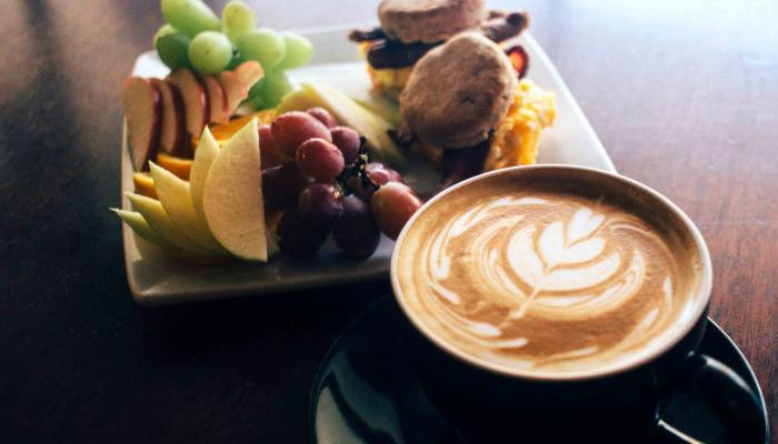 Fruit plate and espresso sitting on a table