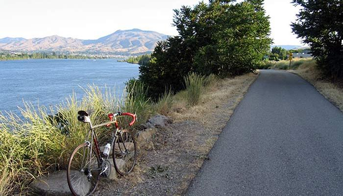 Bike parked next to pavement overlooking columbia river