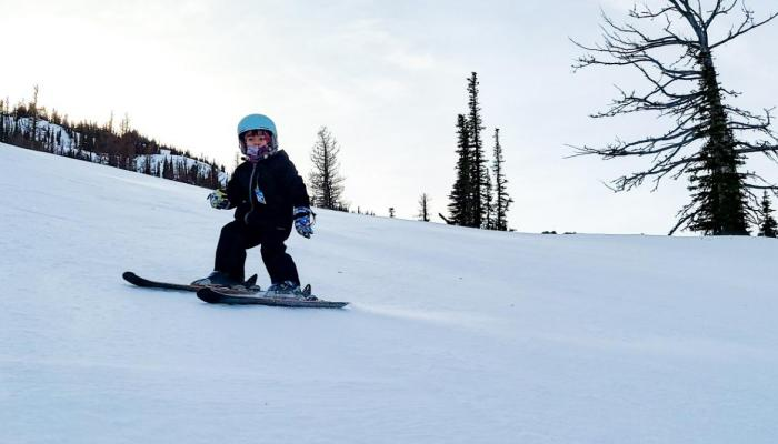 Young skier making turn with sun and trees behind