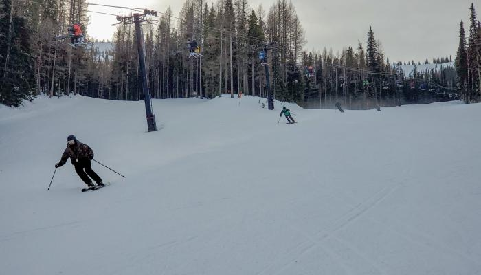 Skiers skiing under chair lift