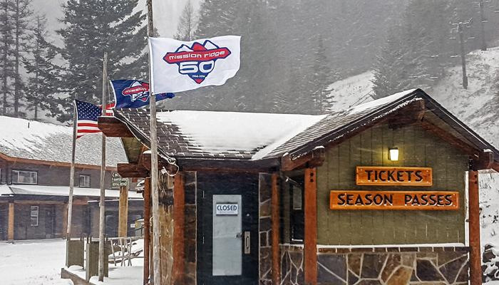 Ticket office with flags fluttering in the wind and snow