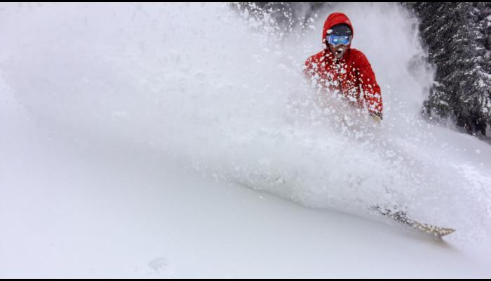 snowboarder making a deep powder turn