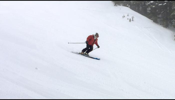 skier on groomed run with trees in background