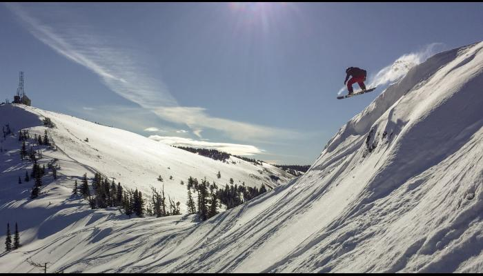 snowboarder dropping off of cornice above powder run