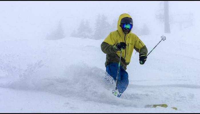skier skiing powder in foggy conditions