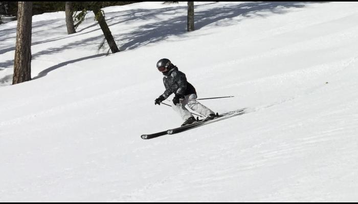 woman skiing groomed run in sunshine