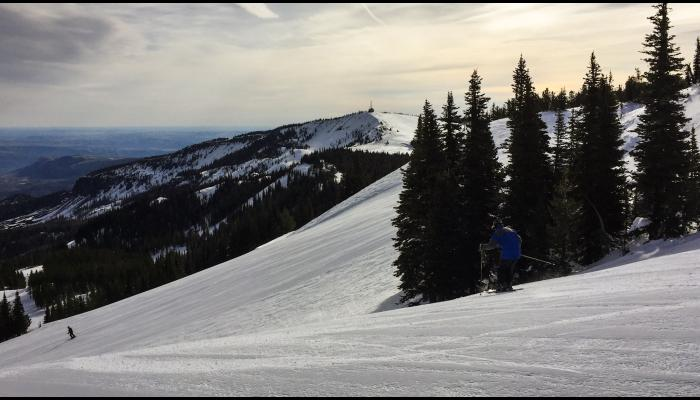 skier on groomed run with windy ridge in background