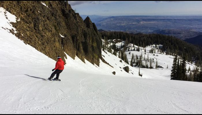 snowboard on sunny groomed run with columbia river in background