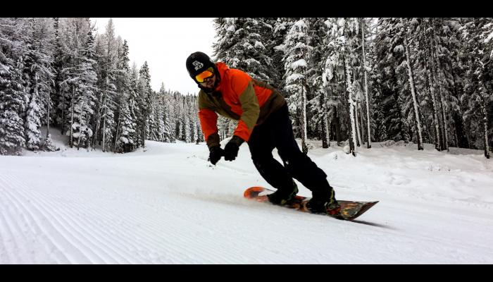 snowboarder in orange and brown jacket riding groomed run
