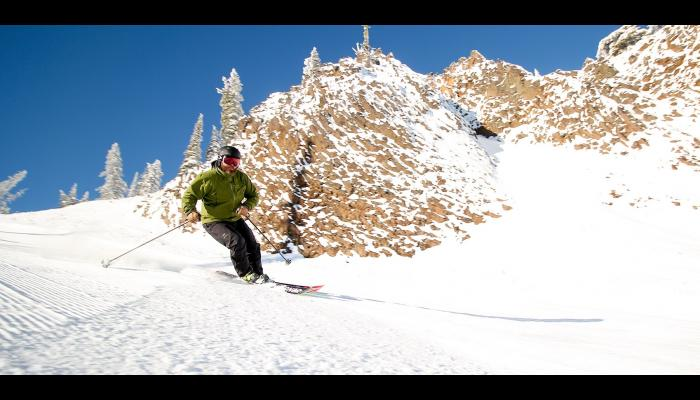 skier in green coat on groomed run with cliffs in background