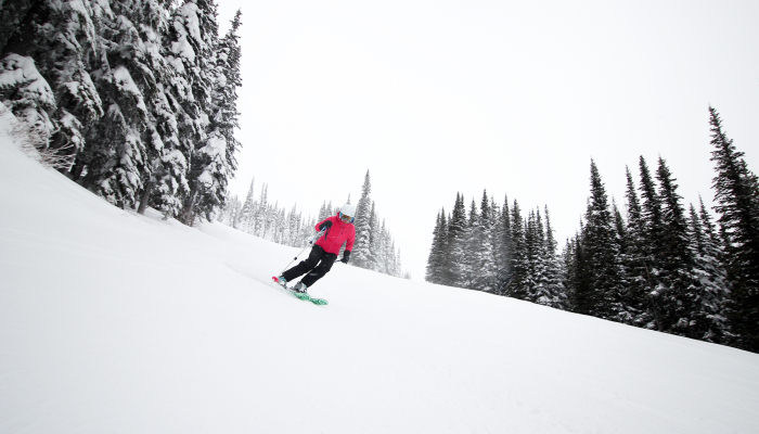 Woman skiing groomed run in bright red jacket.