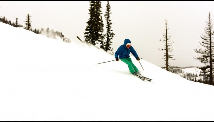 skier on groomed run with trees and cloud in background