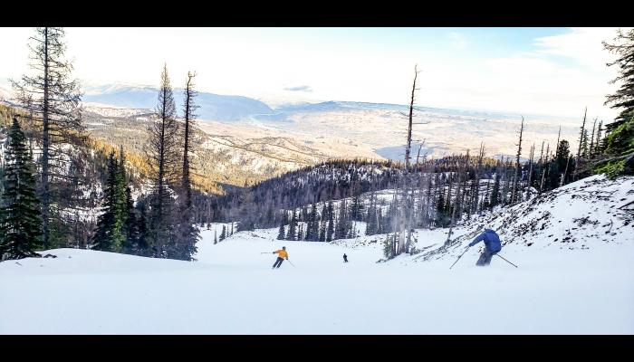 view of the Wenatchee valley as skiers descend a groomed slope