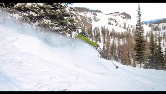skier in powder snow with trees and cliffs in background