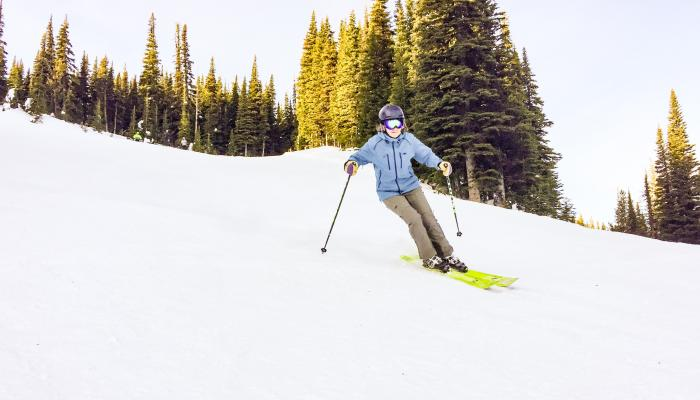 skier on grooomed run with sunny trees in background