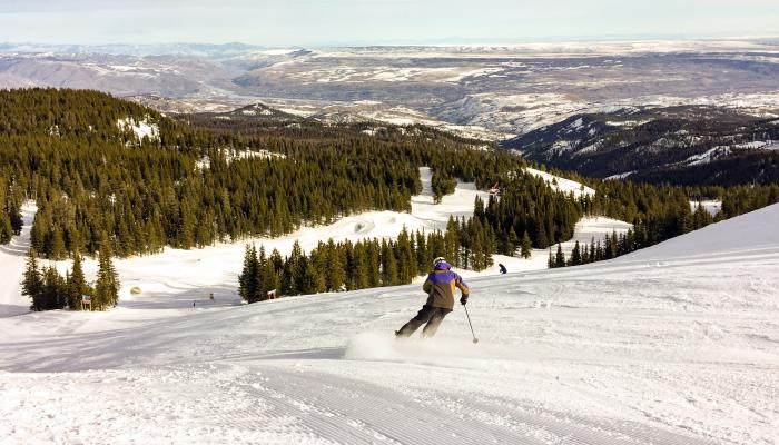 skier descends from the summit of mission ridge with valley view