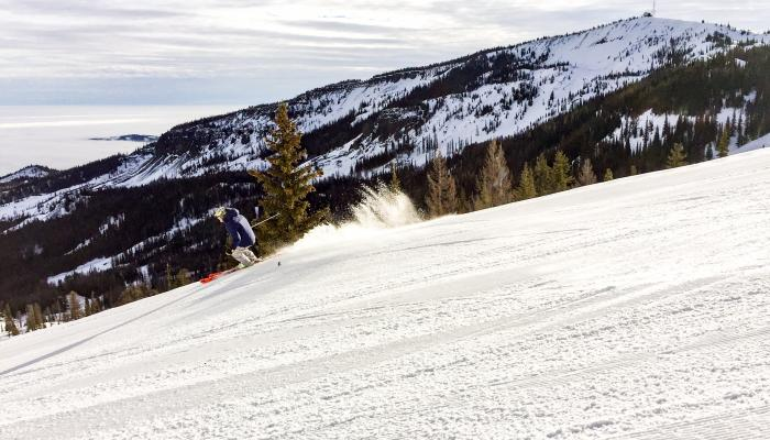 skier on groomed run with wenatchee mountain in background