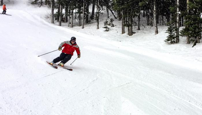 skier carving groomed slope as snow falls