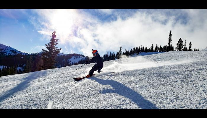 skier on groomed run with sunny mountain scene in background
