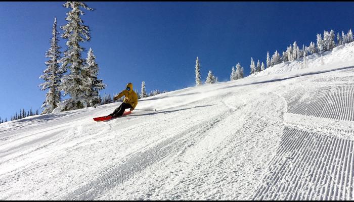 skier carving fresh corduroy under blue skies