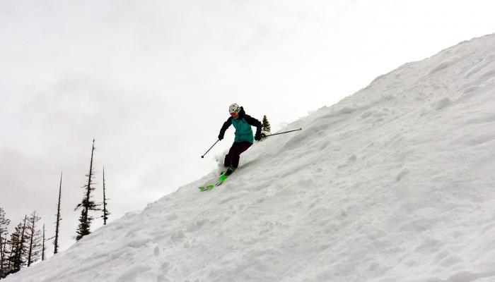 skier on steep slope under cloudy skies