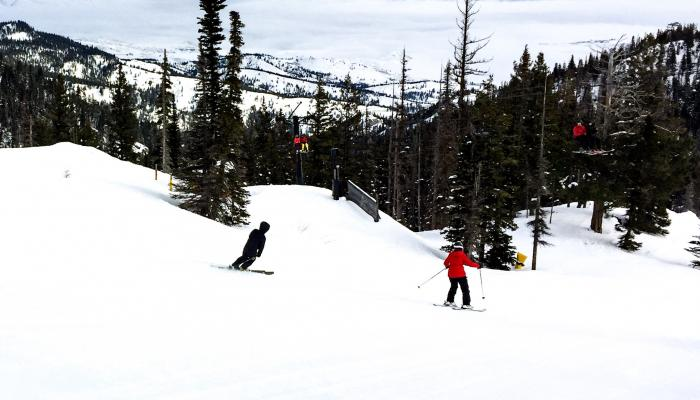 two skiers on groomed run with valley in background