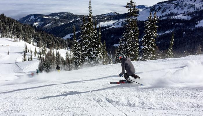 Skier making turn from behind with valley below