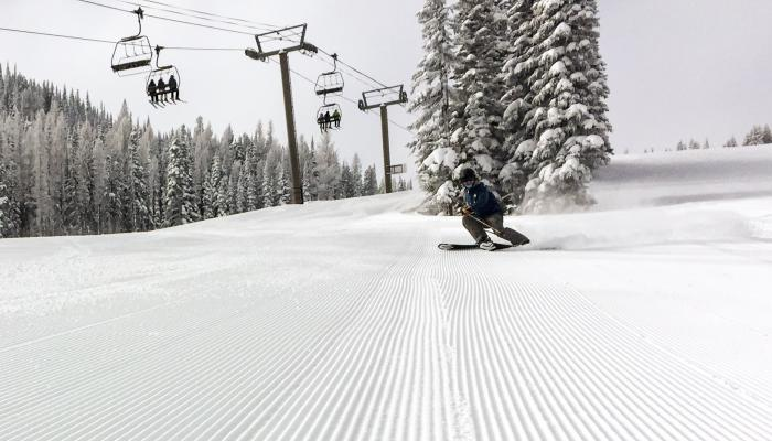 Skier making turn on fresh corduroy with chairlift behind